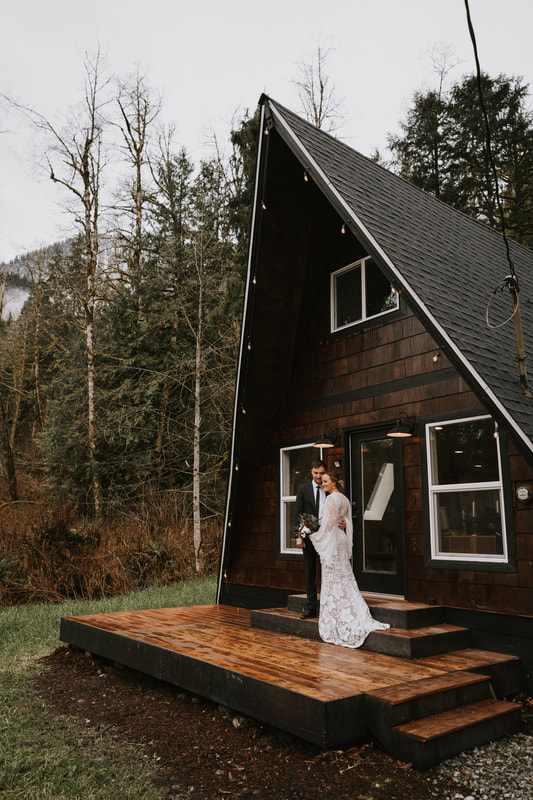 bride and groom in front of pnw cabin